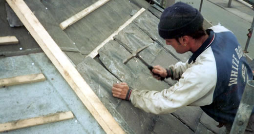 Roofing contractor slating a roof